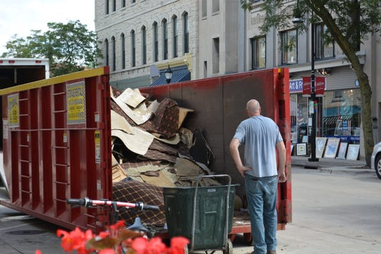 Swatches of damaged carpeting piles up in a commercial trash bin on West Main Street in front of the Clarke Hotel. Smoke accounted for most of the damage, though one room of the hotel will require more work because it was close to the fire found inside the walls on Aug. 14.