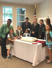 From left, Brownie Emilee Sajban of Vernon, Dr. Bette Simmons of County College of Morris (CCM), Brownie Cecilia Sajban of Vernon, CCM Trustee Chair Paul Licitra, Daisy Zulmarie Briceno of Dover, CCM President Anthony J. Iacono, Assemblyman Anthony M. Bucco, Girl Scout of Northern New Jersey Chief Program Officer Charisse Taylor and Brownie Campbell Burns of Newton cut the cake at the reception announcing the launch of new national badges by the Girl Scouts.
