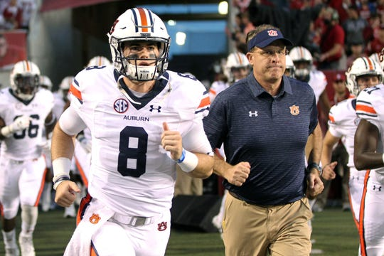 Auburn quarterback Jarrett Stidham (8) and head coach Gus Malzahn run onto the field prior to a game against Arkansas on Oct. 21, 2017, in Fayetteville, Ark.