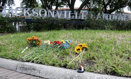 Flowers and a small candle are placed in front of The Jacksonville Landing complex Monday morning. Three people died and numerous were wounded in a shooting during a gaming tournament there over the weekend.