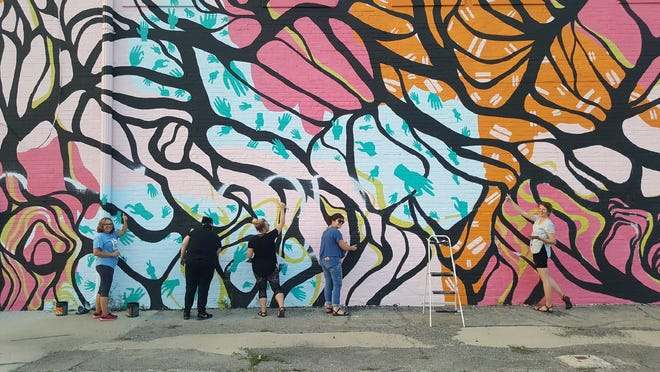A group of volunteers work on restoring downtown Muncie's mural on Wednesday, Aug. 29. The mural, located on the wall of the Mark III Taproom, was vandalized among other places downtown earlier in August.