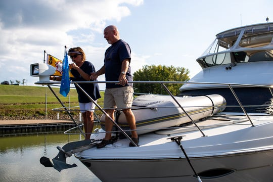 Ron and Karen Atkisson adjust the America's Great Loop Cruisers' Association that flag they received after they crossed their wake on their 7,000-mile journey on America's Great Loop at the Clarksville Marina on Tuesday, Aug. 28, 2018, in Clarksville, Tenn.