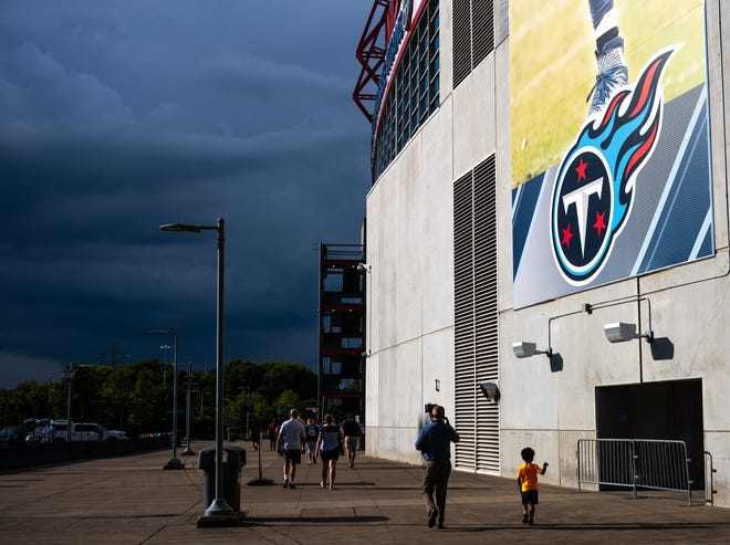 Fans head to the gates as storm clouds are seen in the distance before the game between the Tennessee Titans and the Minnesota Vikings at Nissan Stadium in Nashville, Tenn., Thursday, Aug. 30, 2018.