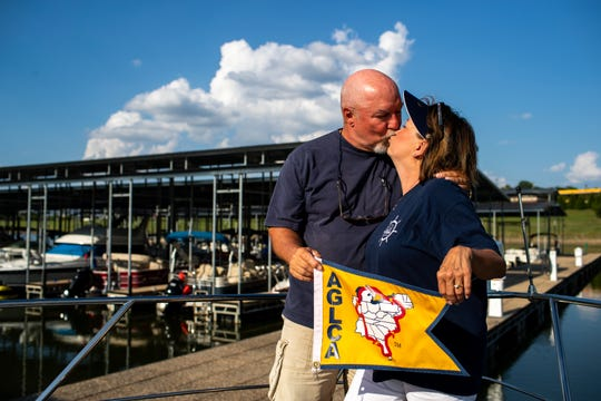 Ron and Karen Atkisson pose for a portrait with the America's Great Loop Cruisers' Association flag that they received after they crossed their wake on their 7,000-mile journey on America's Great Loop at the Clarksville Marina on Tuesday, Aug. 28, 2018, in Clarksville, Tenn.