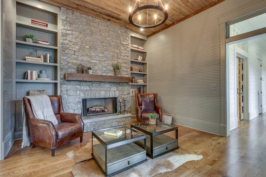 This sitting room just off the kitchen combines reclaimed wood on the ceiling with stone, wood floors and bead board.