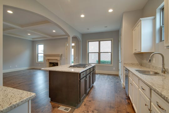 Kitchen islands have become a must-have item in many homes, where they serve as a multi-function hub for meals, school projects and conversation with friends. This is the interior of a newly built Dalamar Homes house.