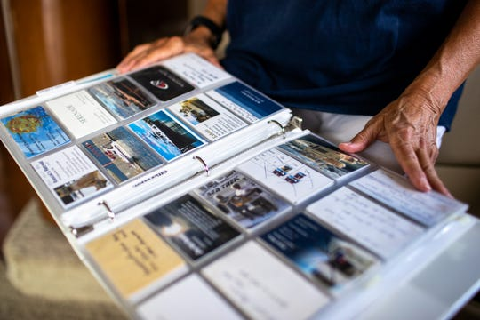 Karen Atkisson looks through cards she and her husband collected during their 7,000-mile journey on America's Great Loop during a stopping point at the Clarksville Marina on Tuesday, Aug. 28, 2018, in Clarksville, Tenn.