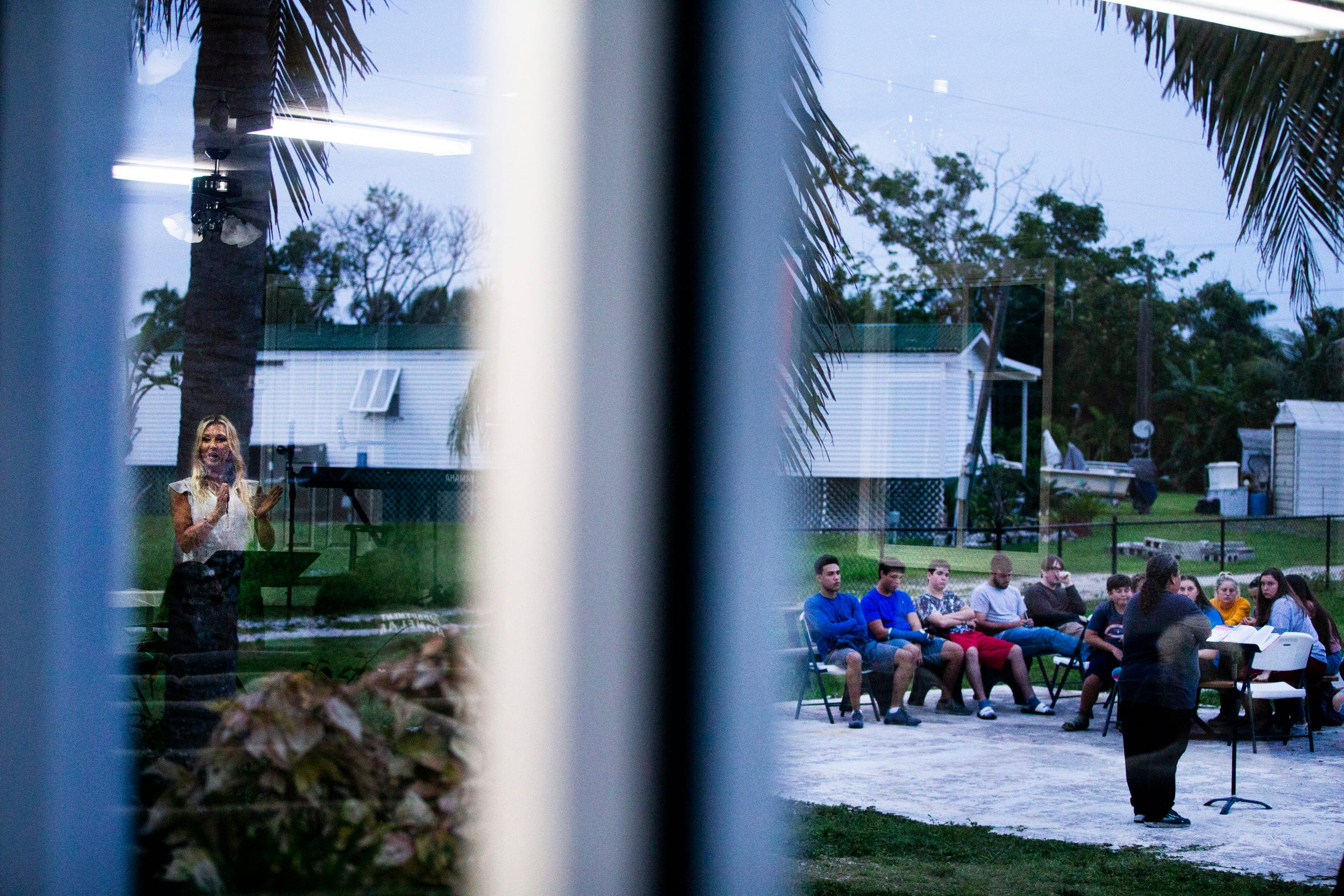 Shannon Mitchell leads the youth group service outside while the Rev. Lynnette Morris, seen reflected in the window, leads the main service inside Chokoloskee Church of God in Chokoloskee on Wednesday, Aug. 29, 2018. Although damage to the church's main building from Hurricane Irma was restored in December, they are still raising funds to rebuild the teen center, which was previously located on the concrete slab seen beneath them.