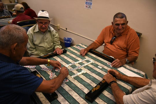NIcodemo Estaban, from left, Carlos Portal, Manuel Felipe and Tomas Lee play a game of dominoes. The Golden Gate Senior Center serves hundreds each week, providing meals, companionship, and a place to meet as well as direct assistance for needy seniors.