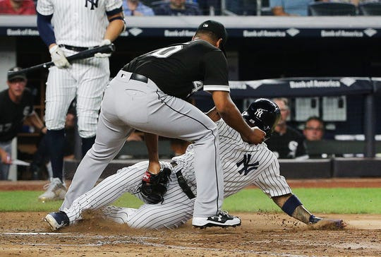 Chicago White Sox starting pitcher Reynaldo Lopez (40) tags out shortstop Gleyber Torres (25) trying to score on a past ball during the fifth inning at Yankee Stadium.