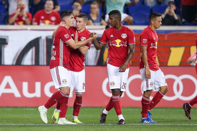 New York Red Bulls forward Brian White (42) celebrates his goal with midfielder Alex Muyl (19) and defender Fidel Escobar (29) during the second half against the Houston Dynamo at Red Bull Arena on Wednesday, Aug. 29, 2018.