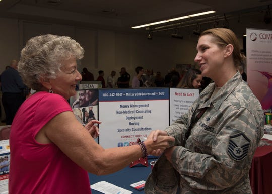Deb Roane, a Military One Source contractor, shakes hands with Master Sgt. Teri B. Ortega, 49th Wing Inspector General superintendent, Aug. 9 in the community activity center on Holloman Air Force Base. Military One Source was one of the job opportunities represented at Hring Our Heroes, created to help Airmen transitioon into civilian life.