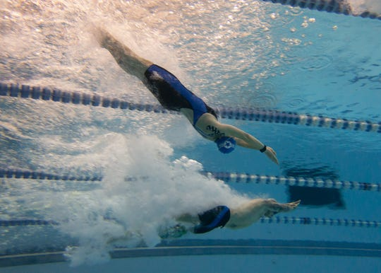 Master Sgt. Lisa Goad completes a backstroke dive while Technical Sergeant Derrall Peach Jr. dives in for a freestyle swim practice at the DoD Warrior Games 2018.