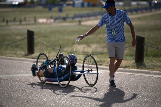 Air Force Coach Aaron Moffett pours water over an athlete during the 2018 DoD Warrior Games cycling competition at the Air Force Academy in Colorado Springs, Colo. June 6.