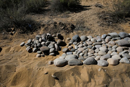 Materials for a trail being constructed by members of the New Mexico Youth Conservation Corps in conjunction with Capacity Builders are piled Thursday along Navajo Route 365 near the Nenahnezad Chapter house.