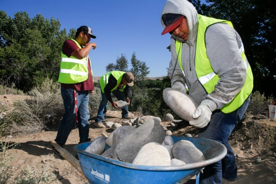 Youth Conservation Corps members Lance Joe, left, Shyler Becenti and Rory Henry load a wheelbarrow with rocks Thursday near the Nenahnezad Chapter house.