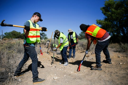 Members of the New Mexico Youth Conservation Corps construct a trail, Thursday, Aug. 30, 2018 along Navajo Route 365 near the Nenahnezad Chapter House.