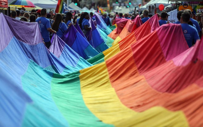A rainbow flag is carried down Palm Canyon Drive during the annual Palm Springs Pride parade. Richard Lui/The Desert Sun