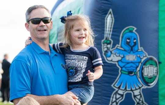 Jason Crawford and his daughter Olivia, 3, listen to the Argos band prior to the University of Florida's first football game of the season at Blue Wahoos Stadium in Pensacola on Thursday, August 30, 2018.