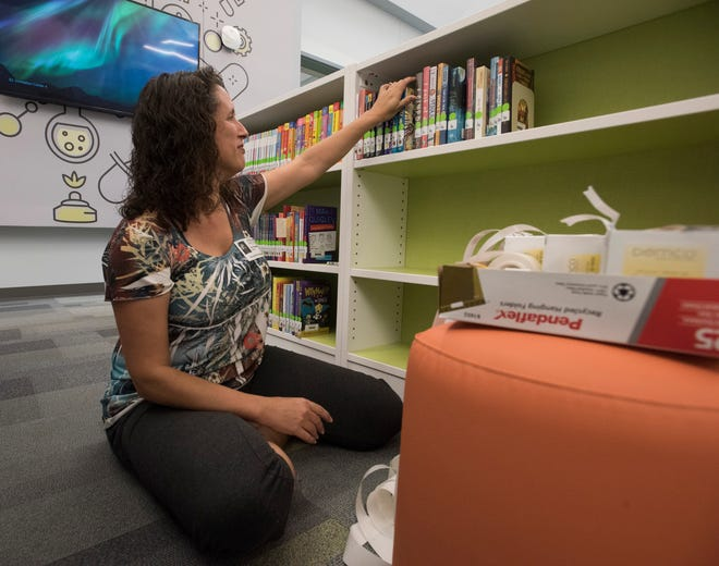 Lisa Newbern volunteers her time cataloging the bookshelves in the Innovation Center at the new Kingsfield Elementary School on Thursday, Aug. 30, 2018. The Escambia County School District celebrated with a grand opening of the new elementary school with a ribbon cutting ceremony on Thursday, Aug. 30, 2018.