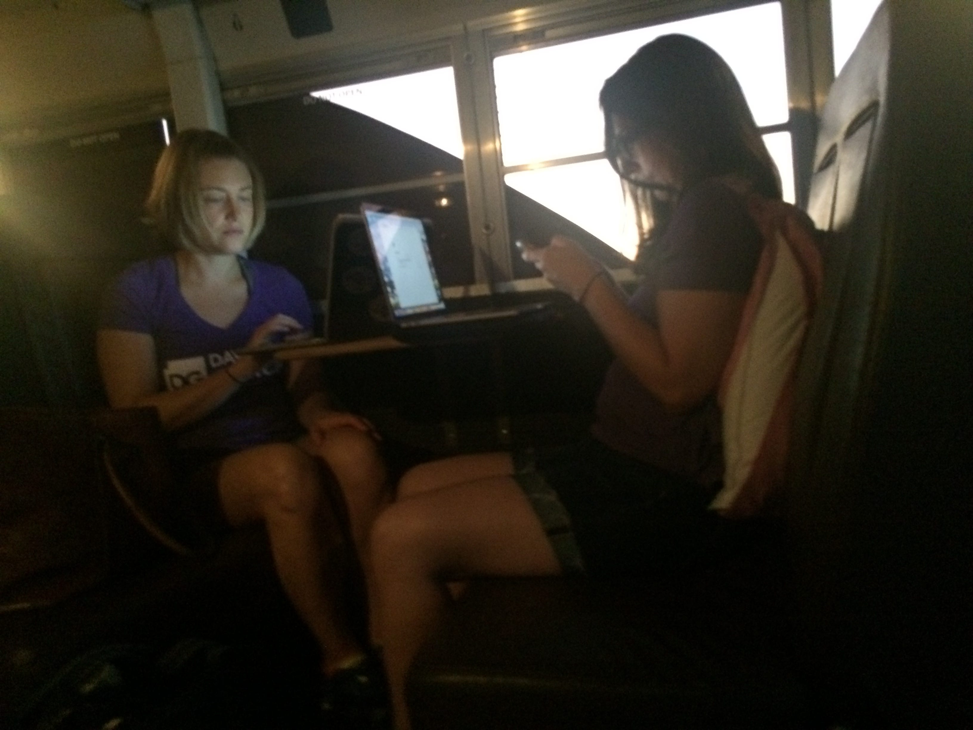 Staff members for the David Garcia gubernatorial campaign, Meghan Gutekunst (left), fundraising manager, and Sarah Elliott, communications director, work on laptops and cellphones during a trip to Douglas on Aug. 19, 2018. Garcia converted a school bus for campaign use.
