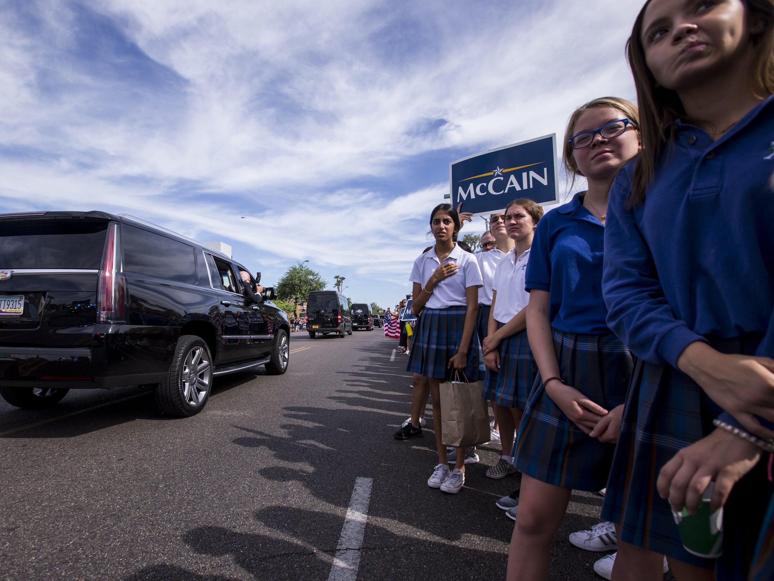 Xavier students watch as Sen. John McCain's motorcade passes by on the way to his Arizona Memorial Service at North Phoenix Baptist Church on Thursday, Aug. 30, 2018, in Phoenix.
