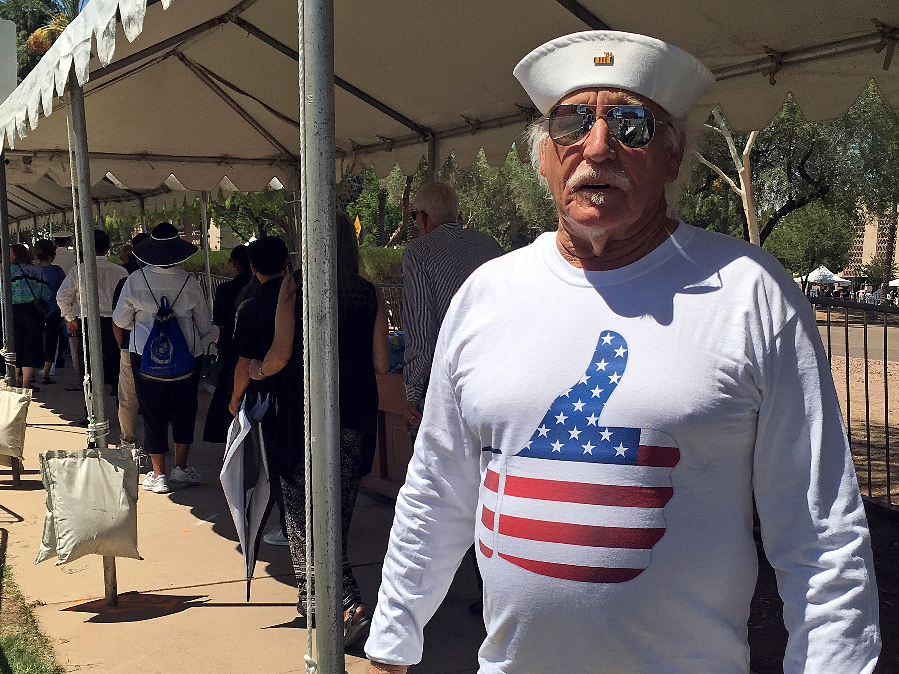 Louis Albin, an artist in Phoenix and Navy veteran, displays his custom-made T-shirt as he waits in line for the public viewing of the late Sen. John McCain Aug. 29, 2018, outside the Arizona Capitol. The shirt, which features an image of a thumbs-up covered in the stars and stripes of the flag, is a play on McCain's thumb-down vote that sank President Donald Trump's repeal of the Affordable Care Act. Albin turned the thumb up as a wink to McCain's vote, which Albin approved of.