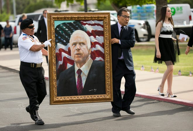 A portrait of Sen. John McCain is carried to North Phoenix Baptist Church before McCain's memorial service at North Phoenix Baptist Church in Phoenix on Thursday, August 30, 2018.