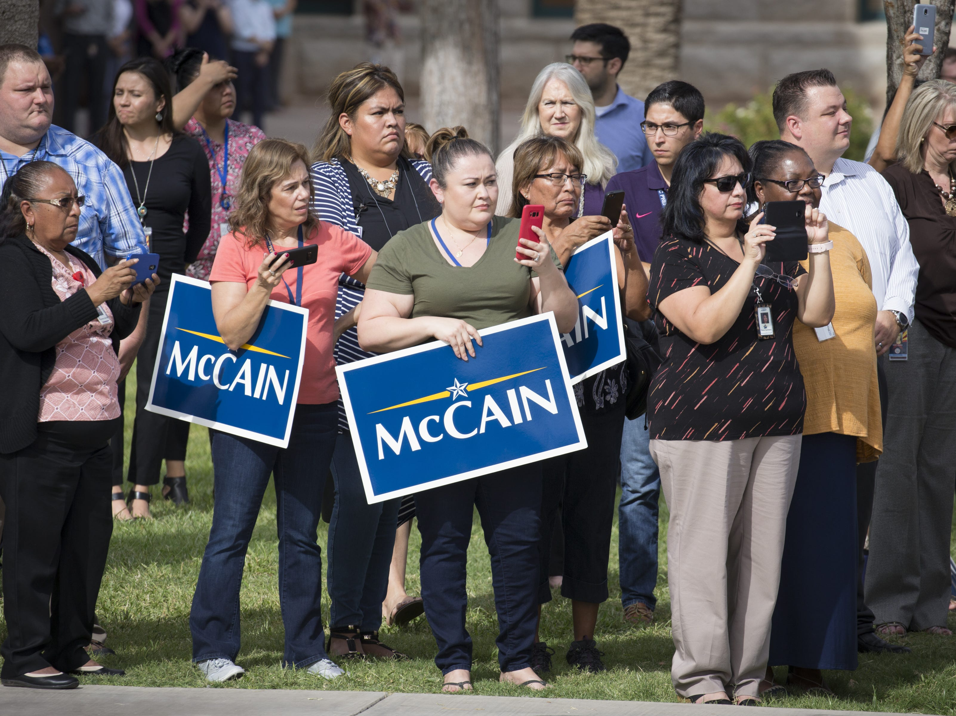 McCain supporters watch the casket carrying the body of John McCain leave the Arizona State Capitol, Aug. 30, 2018, for the memorial service at North Phoenix Baptist Church, Phoenix, Arizona.