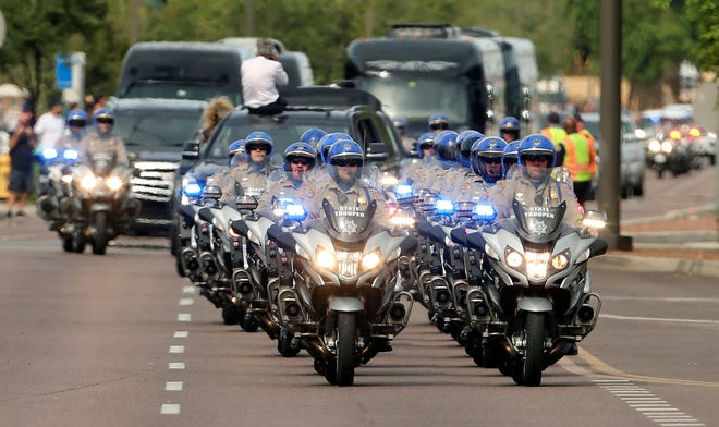 Arizona State Troopers escort the motorcade carrying Sen. John McCain, R-Ariz., as it makes its way to a memorial service, Aug. 30, 2018, in Phoenix.