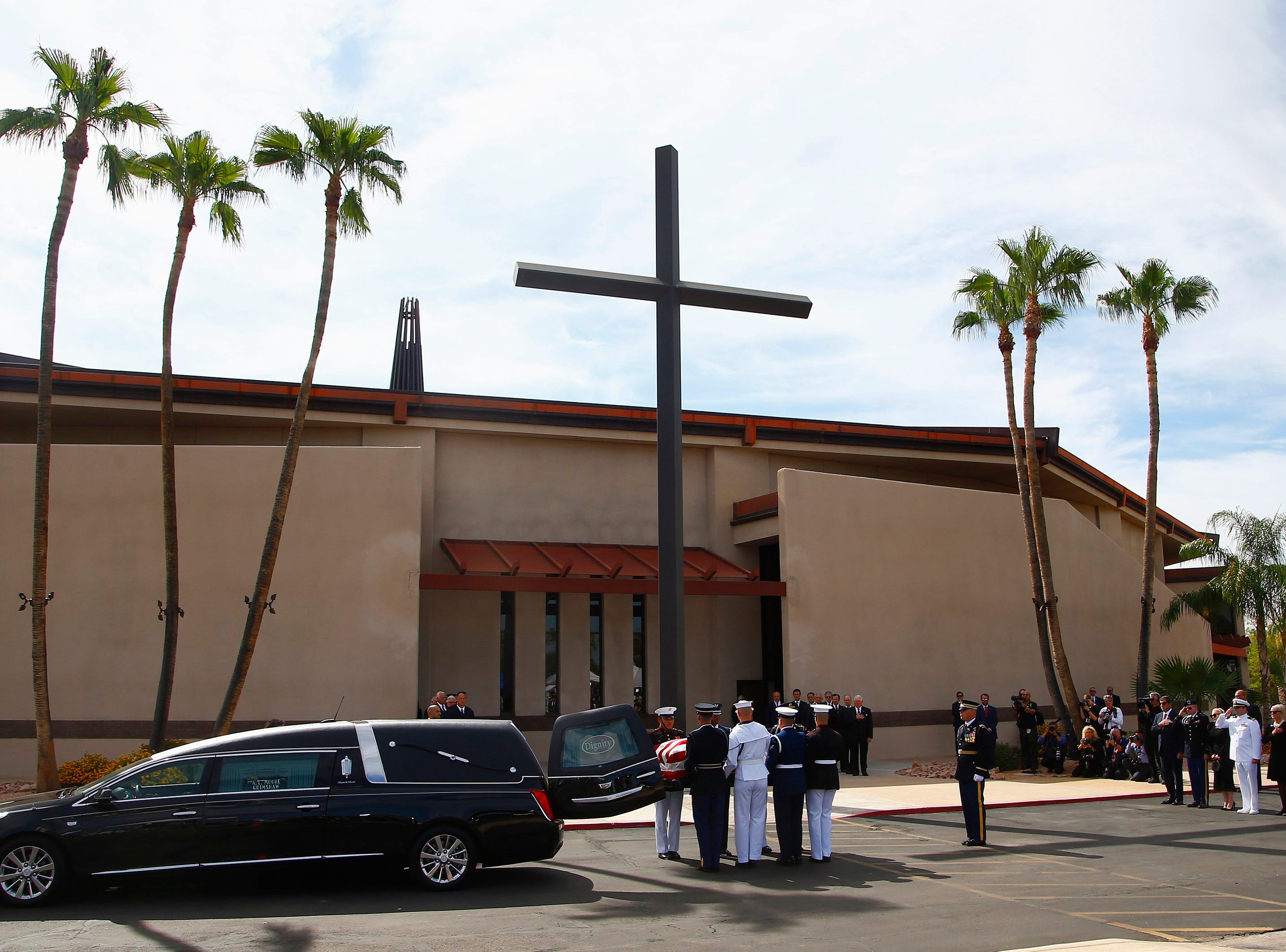 A military team removes the casket carrying Sen. John McCain, R-Ariz., from the hearse prior to a memorial service at North Phoenix Baptist Church as McCain's immediate family watches, right, Aug. 30, 2018, in Phoenix.