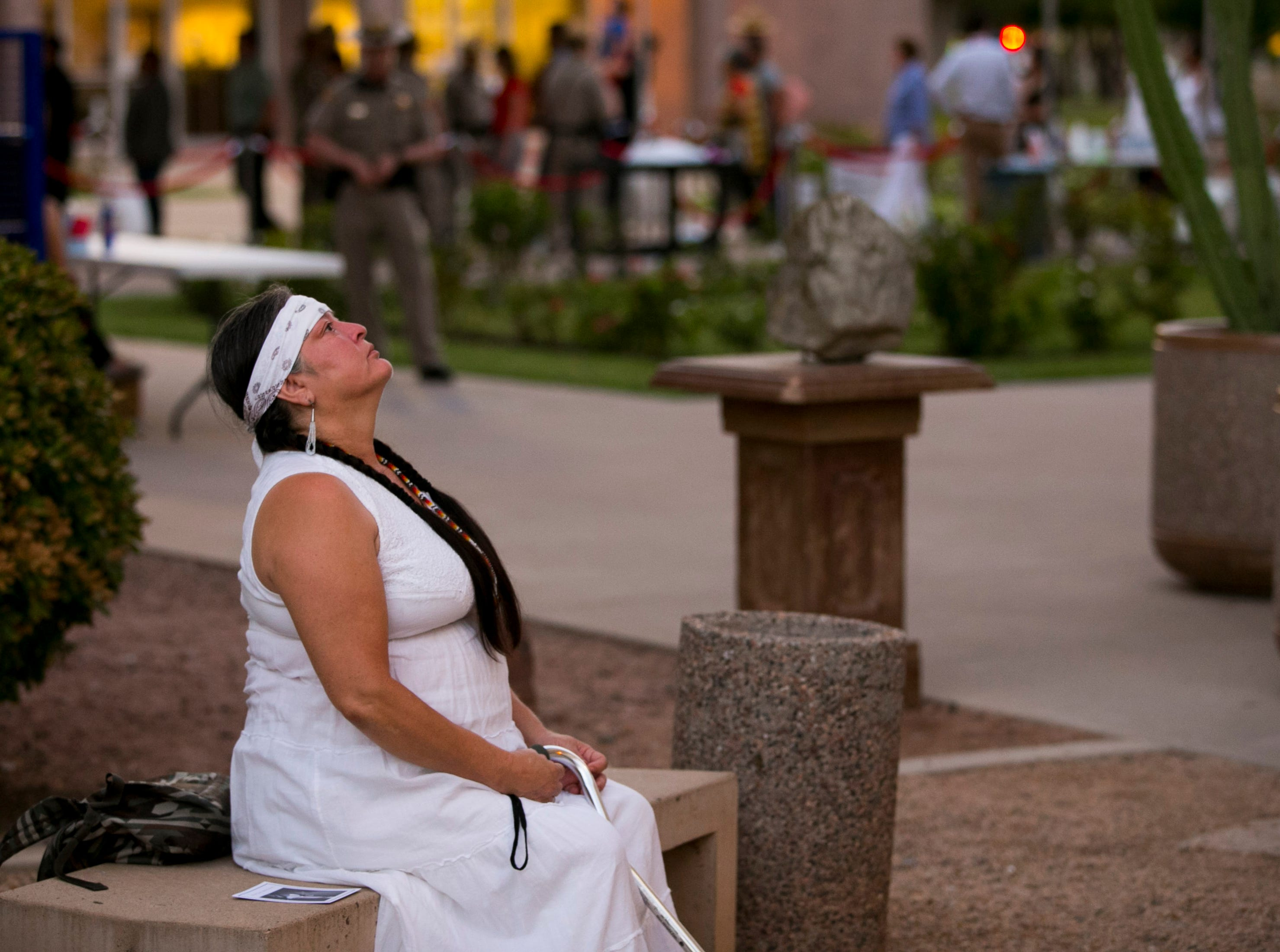 Dehliah Alvidrez of Phoenix, spends a moment to herself on a bench just outside the Arizona state capitol after paying her respects where Senator John McCain lies in state in Phoenix on Wednesday, August 29, 2018.
