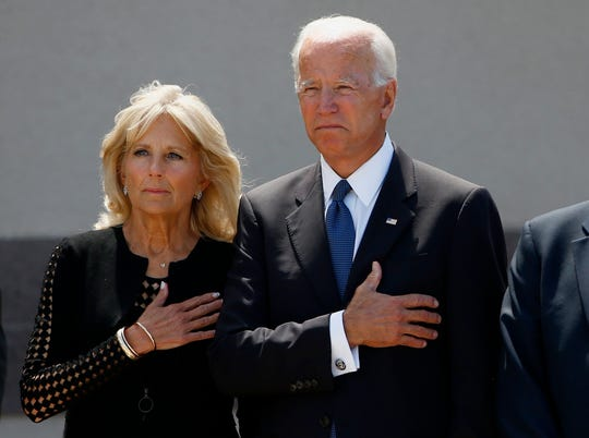 Former Vice President Joe Biden, right, and his wife Jill Biden, pause with hands over their hearts as they watch a military honor guard place the casket of Sen. John McCain, R-Ariz., into a hearse after a memorial service at North Phoenix Baptist Church, Aug. 30, 2018, in Phoenix.