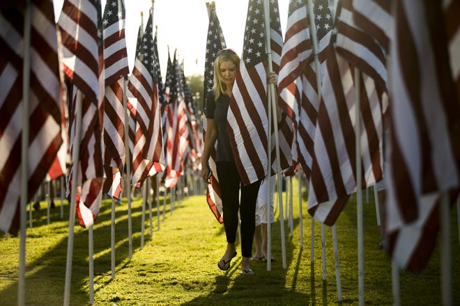 Tina Barton of Gilbert, carries an American flag while hundreds of volunteers set up the American flags for the 13th annual 9/11 Healing Field at Tempe Beach Park on September 9, 2016. The Healing Field memorializes the terrorist attacks of September 11, 2001, with a flag for every victim who died as a result of the terrorist attacks.
