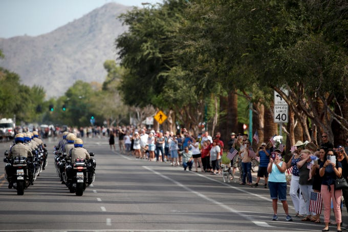 People watch the motorcade carrying the casket of Sen. John McCain, R-Ariz., from the Arizona Capitol to the North Phoenix Baptist Church for a memorial service on Aug. 30, 2018, in Phoenix.