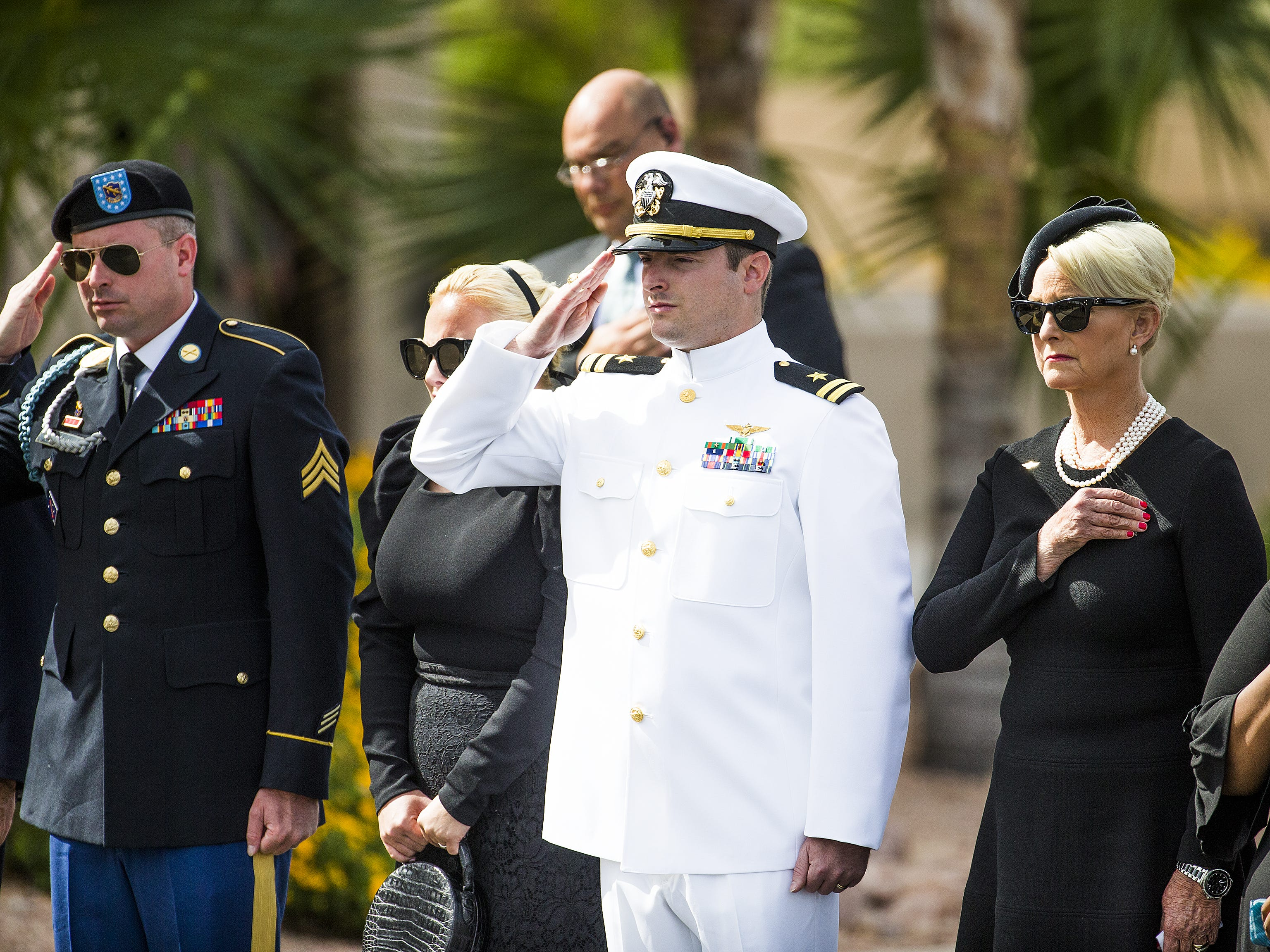 The McCain family, Jimmy, Meghan, Jack, Cindy and Bridget salute as the casket of Sen. John McCain is taken from the hearse at the North Phoenix Baptist Church in Phoenix, Aug. 30, 2018.