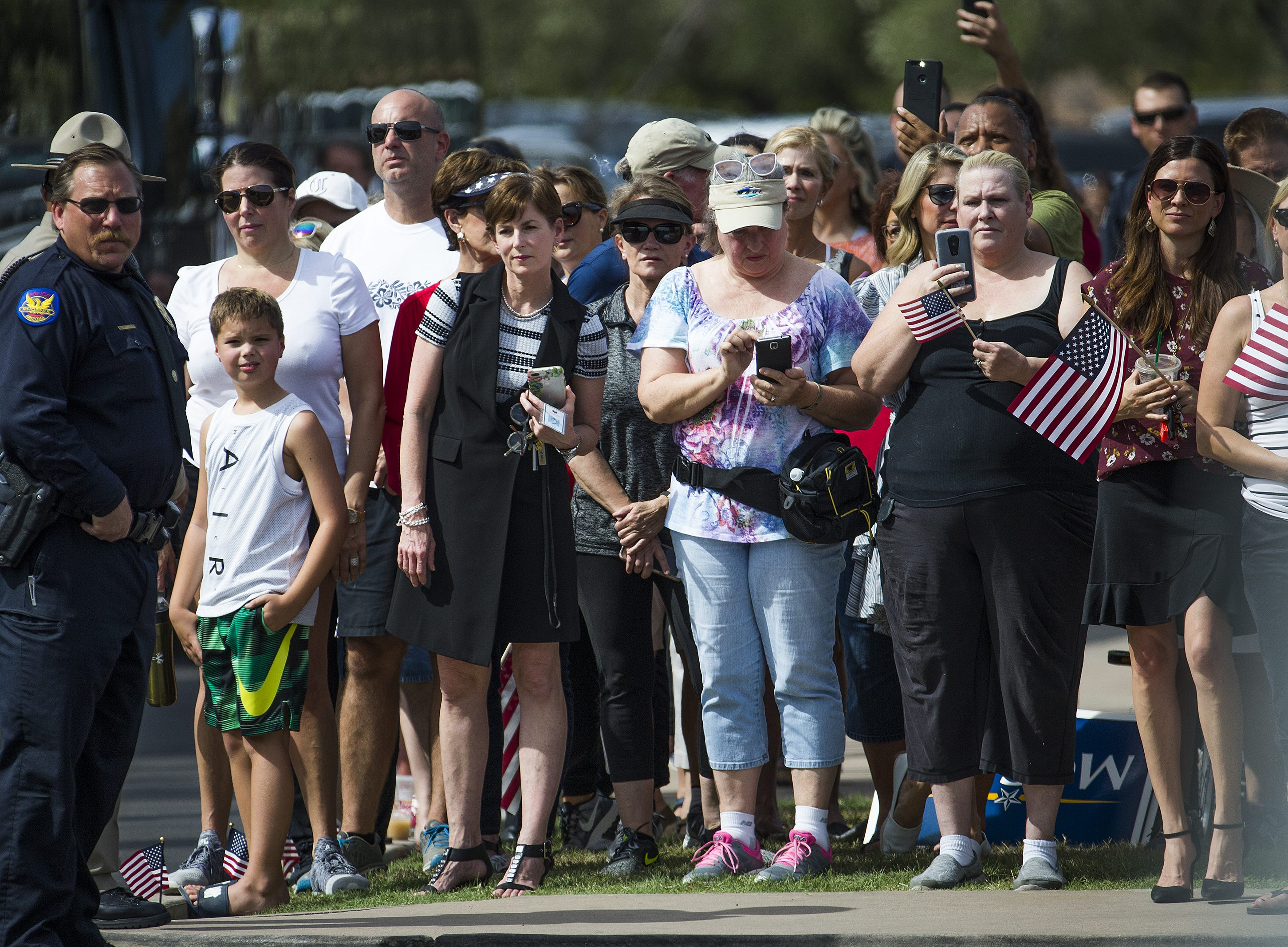 A crowd watches as the casket of Sen. John McCain is taken from the hearse at the North Phoenix Baptist Church in Phoenix, Aug. 30, 2018.