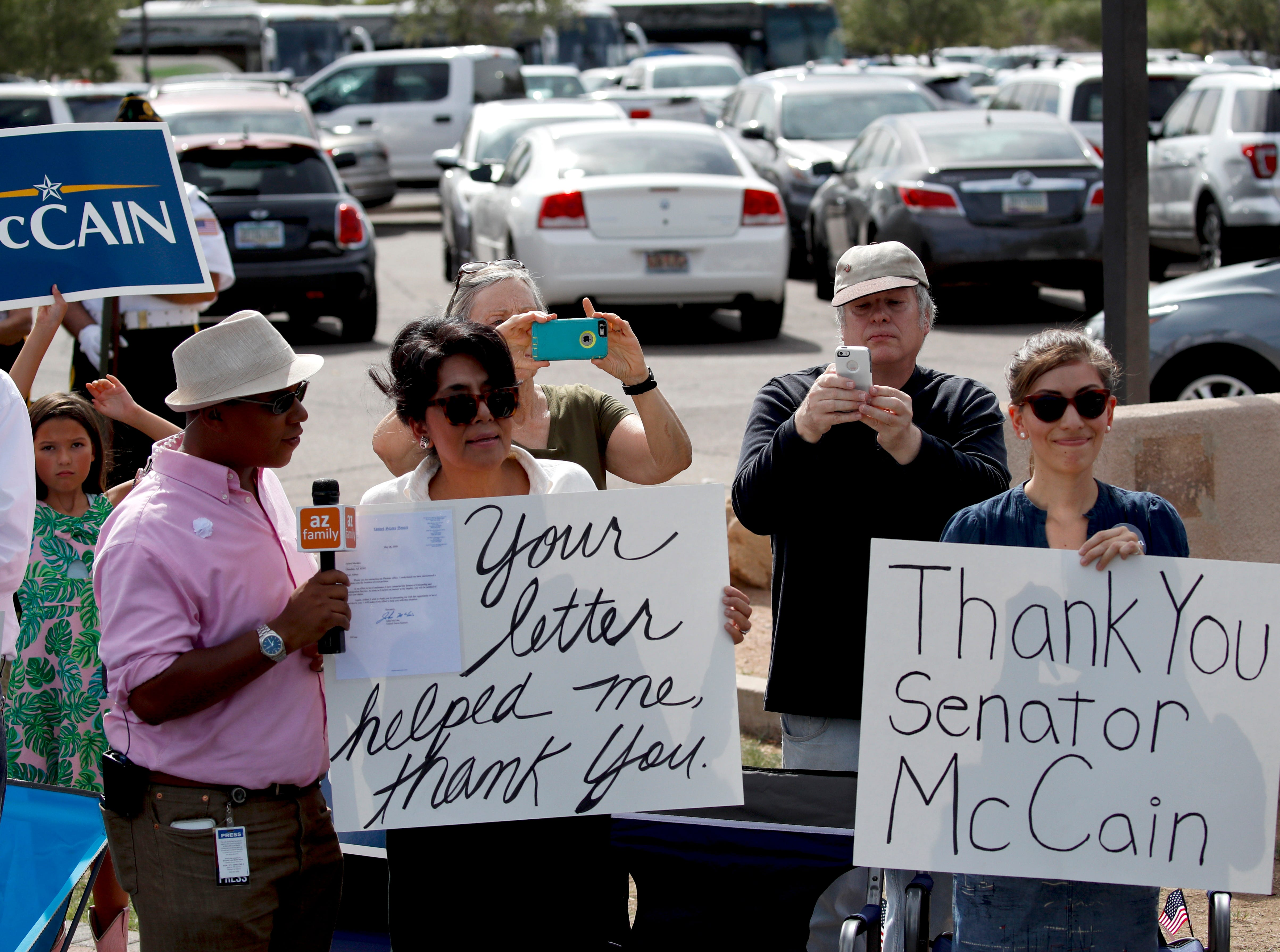 People watch the motorcade carrying the casket of Sen. John McCain, R-Ariz. from the Arizona Capitol to the North Phoenix Baptist Church for a memorial service on Aug. 30, 2018, in Phoenix.