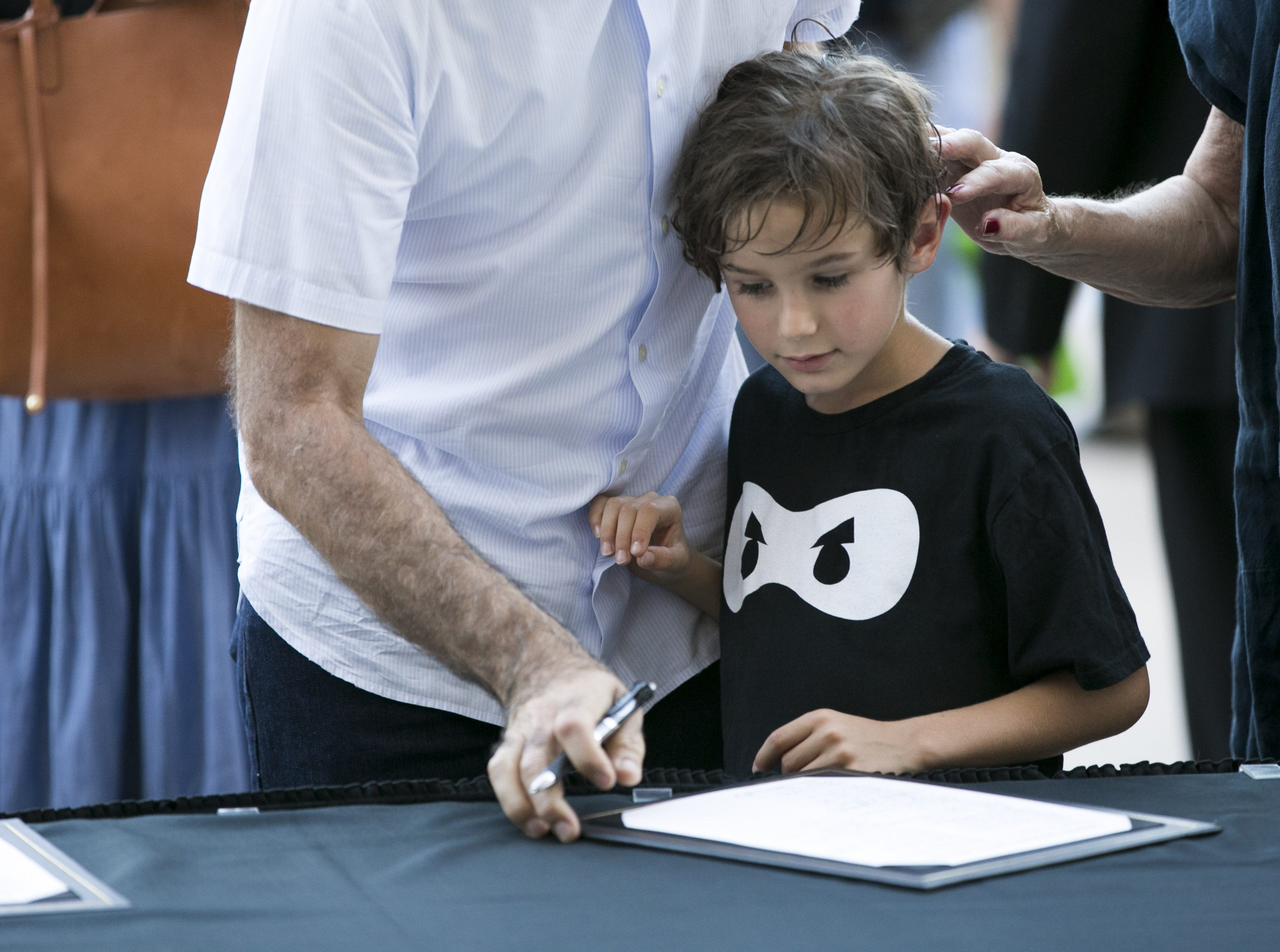 Oliver Solis, 6, of Phoenix, signs a guest book before entering the Arizona Capitol building where Senator John McCain lies in state in Phoenix on Wednesday, August 29, 2018.