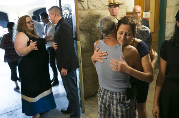 Sidney McCain, the daughter of Sen. John McCain, hugs a man who came to pay his respect to their father as they wait in line to enter the Arizona state capitol where Senator John McCain lies in state in Phoenix on Wednesday, August 29, 2018.