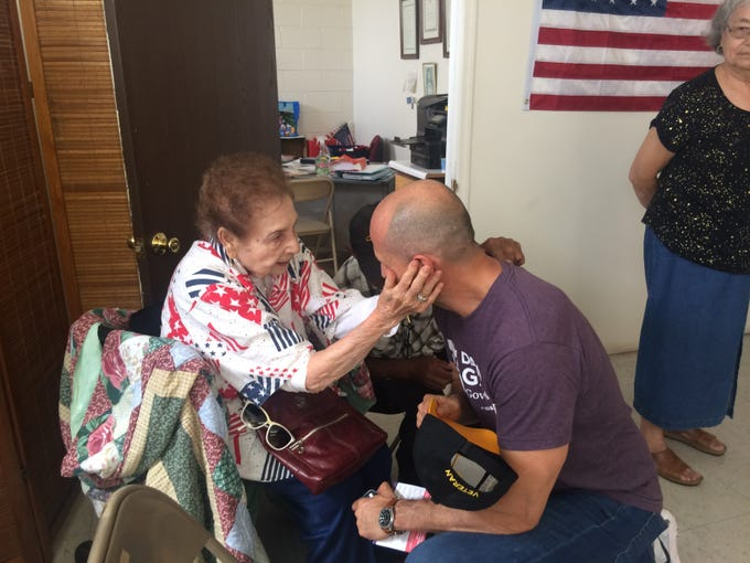 David Garcia, Democratic candidate for Arizona governor, kneels to receive a blessing from Lupe Garcia, 92, at the St. Vincent de Paul hall in Douglas on Aug. 19, 2018. Lupe Garcia was born and raised in Douglas and used to drive residents to the polls on Election Day.