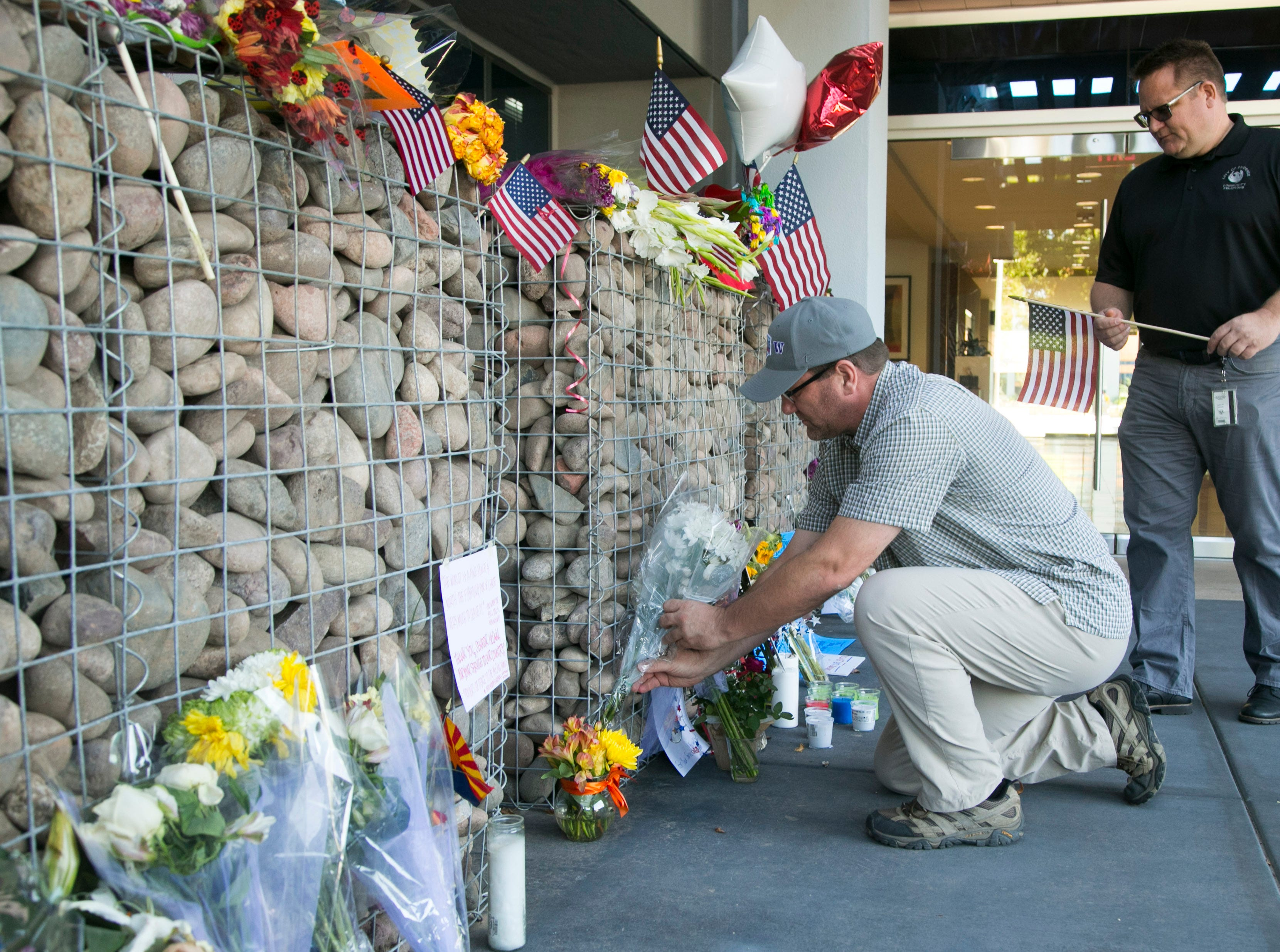 James Olsen (bottom) of Columbia, S.C., and his brother, Ted Olsen of Phoenix, place flowers and an American flag at a memorial for Sen. John McCain at McCain's office in Phoenix on Monday morning, August 27, 2018.
