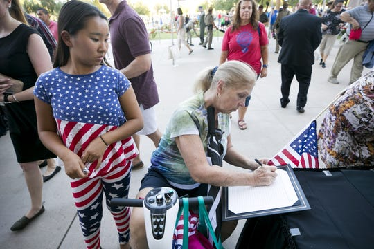 Jeananne Larson of Scottsdale and her daughter, Dana Larson, 16, sign a guest book before entering the Arizona Capitol where Senator John McCain lies in state in Phoenix on Wednesday, August 29, 2018.