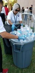Organizers offer water to those waiting in line to pay their respects to Sen. John McCain at the Arizona Capitol.