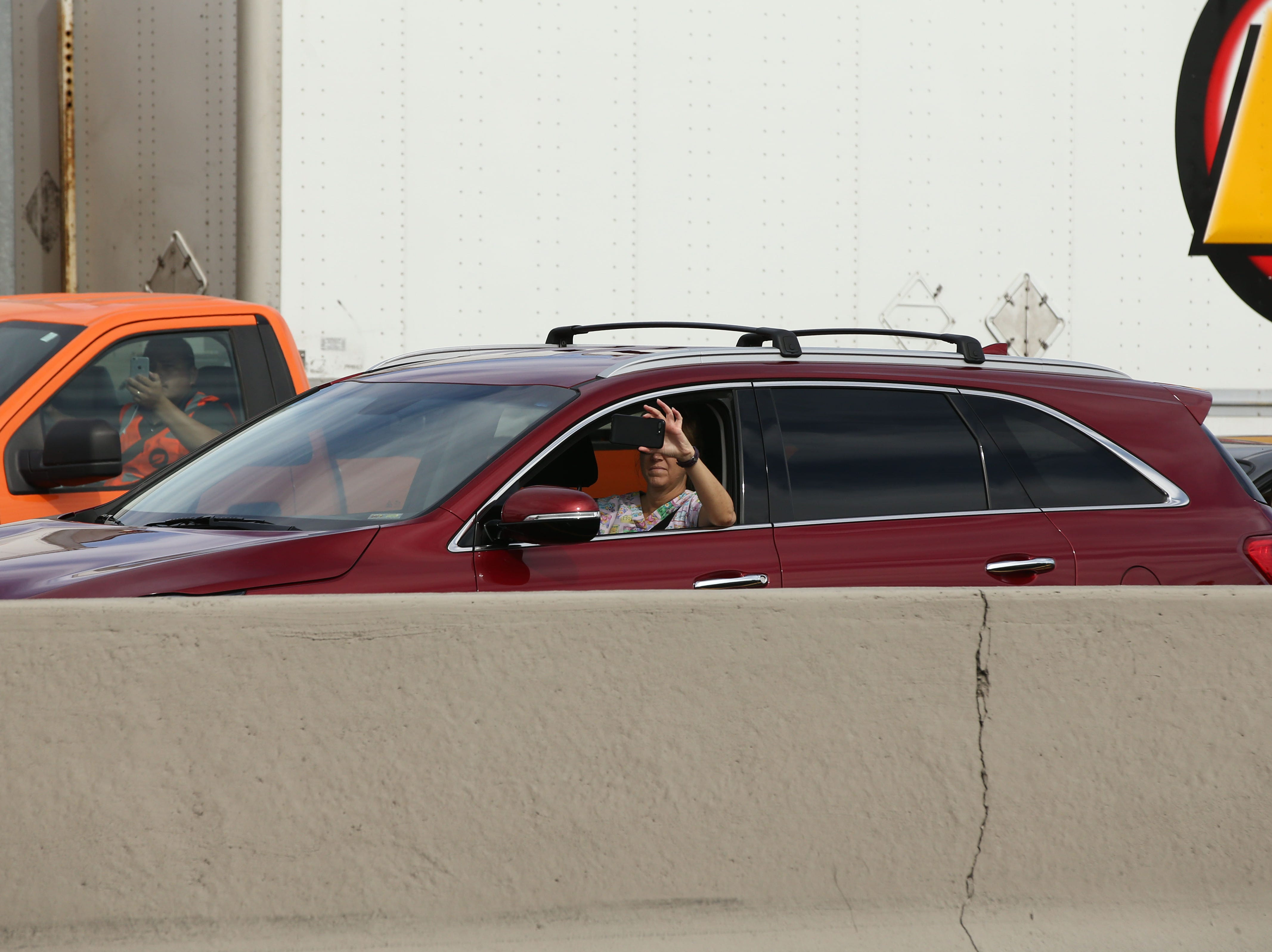 People stopped on I-17 pay their final respects as the hearse of U.S. Senator John McCain traveled to his memorial service at North Phoenix Baptist Church on Aug. 30, 2018,in Phoenix.
