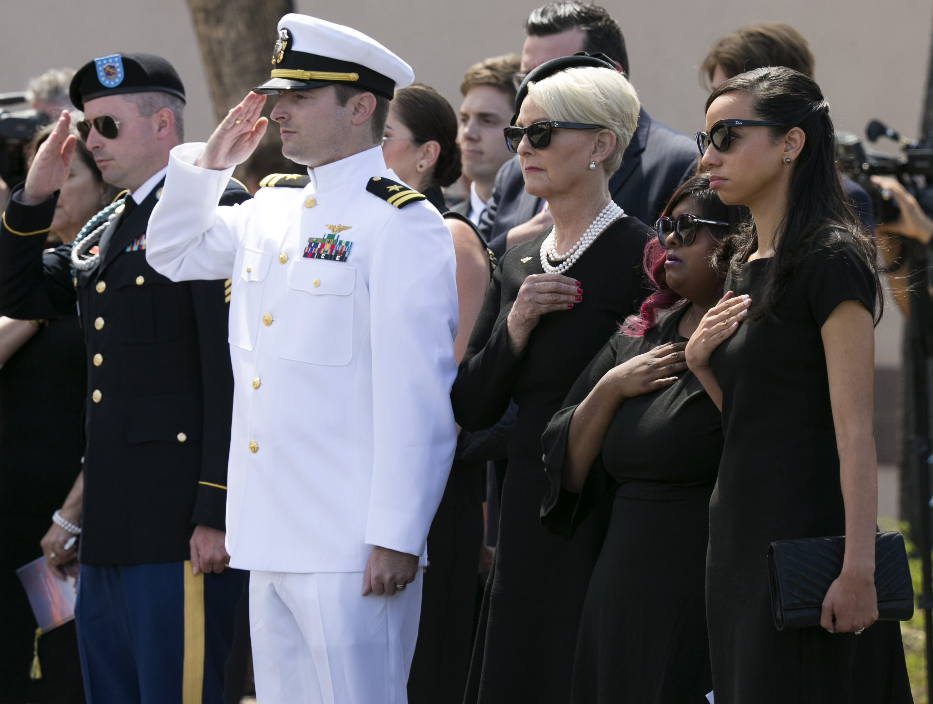 Senator John McCain's family (from left) Jimmy McCain, Jack McCain, Cindy McCain, Bridget McCain and Renee McCain, salute and place their hands on their hearts as the casket of Sen. McCain is placed in the hearse following a memorial service for Senator McCain at North Phoenix Baptist Church in Phoenix, Aug. 30, 2018.