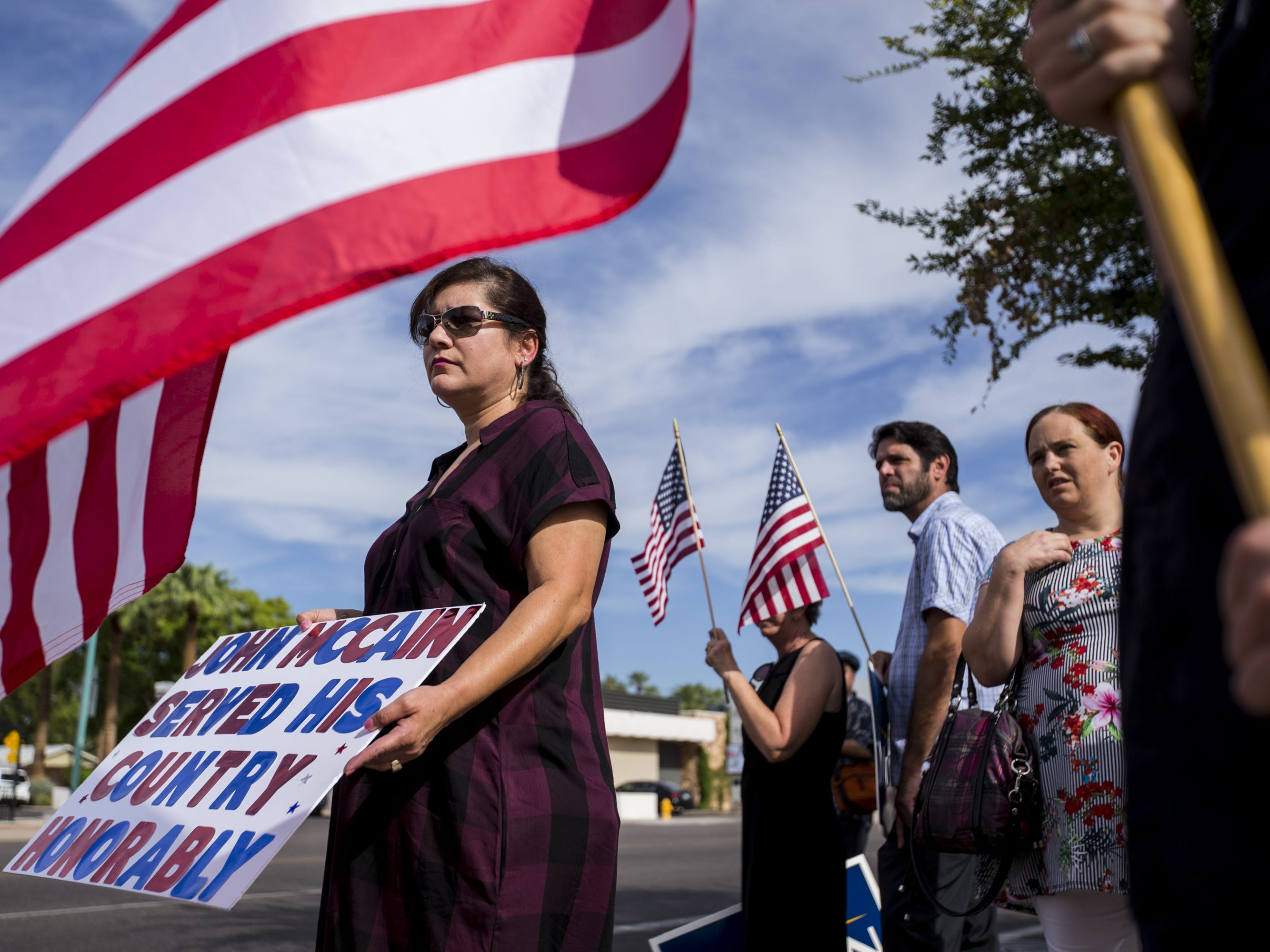 Melissa Arvizo holds a sign for John McCain on Central Avenue north of Camelback Road along the motorcade route to his Arizona Memorial Service at North Phoenix Baptist Church, Aug. 30, 2018, in Phoenix.