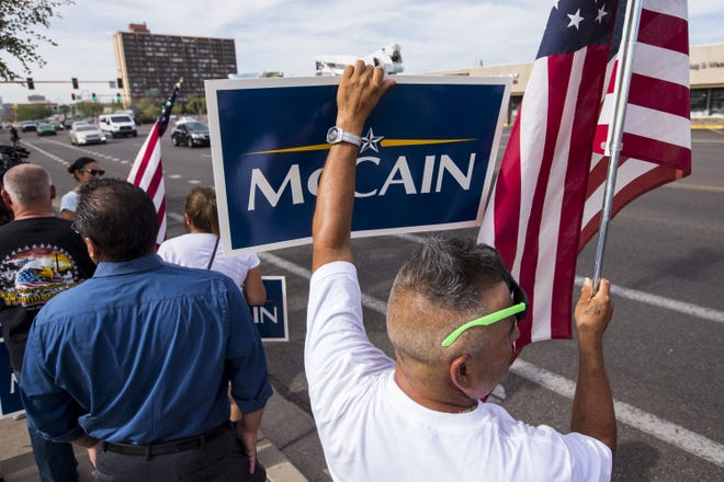 People hold McCain signs on Central Avenue north of Camelback Road along Sen. John McCain's motorcade route to his Arizona Memorial Service at North Phoenix Baptist Church, Aug. 30, 2018, in Phoenix.