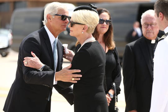 Cindy McCain hugs Rick Davis on Aug. 30, 2018, during the transfer ceremony for Sen. John McCain at the Goldwater Air National Guard Base at Sky Harbor International Airportin Phoenix. Sen. McCain's casket was placed onboard a C-32 military aircraft to depart Arizona for the last time.