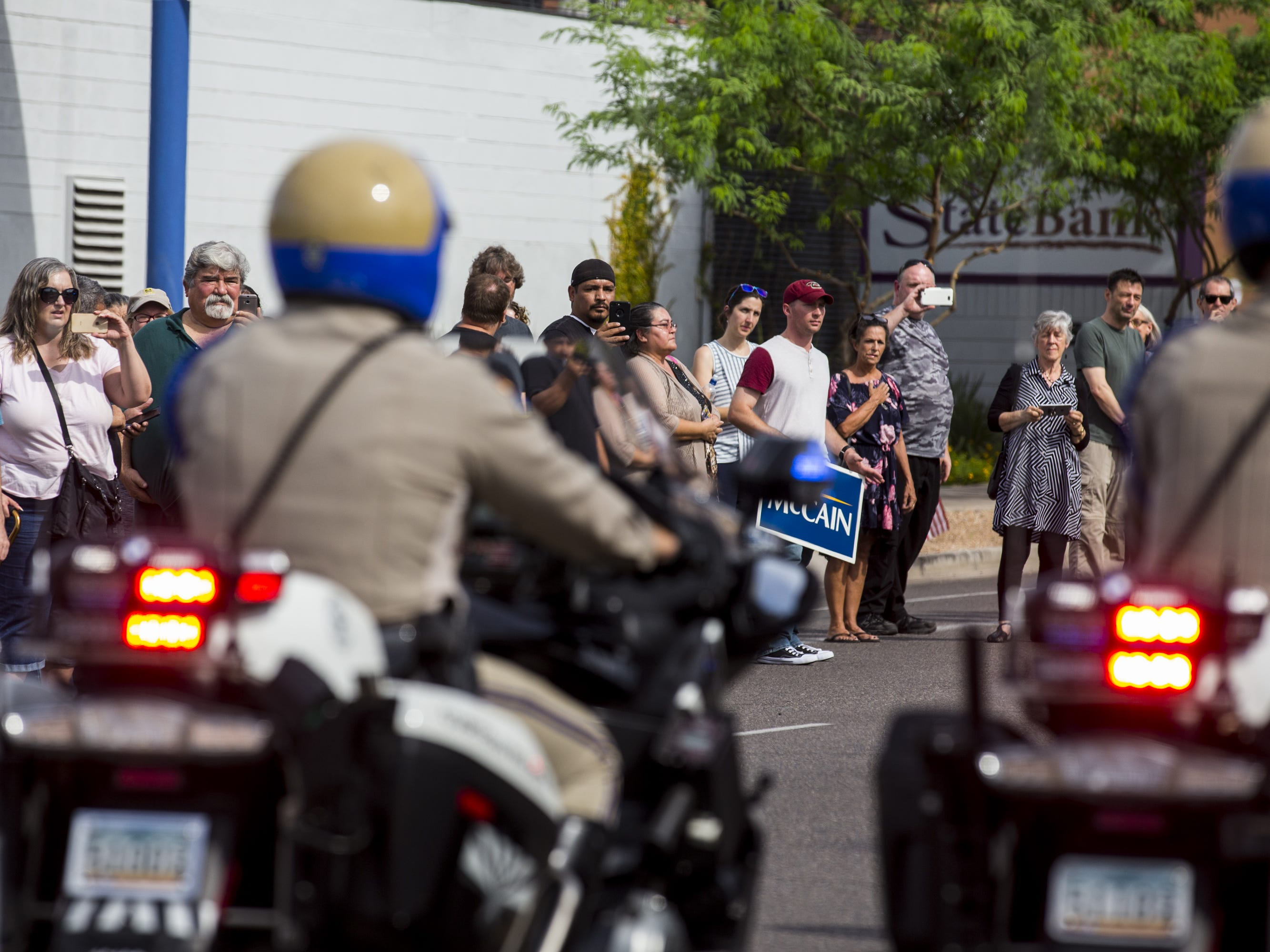 People watch as the motorcade escorting Sen. John McCain's body drives north on Camelback Road on the way to his Arizona Memorial Service at North Phoenix Baptist Church, Aug. 30, 2018, in Phoenix.
